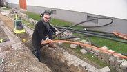 Der Bürgermeister von Karlsdorf mit zwei Glasfaserleitungen in der Hand.