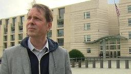 ARD-Reporter John Goetz steht vor der amerikanischen Botschaft in Berlin.