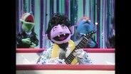 Graf Zahl mit einer Elvis-Tolle und Gitarre, dahinter Backgroundsänger.
