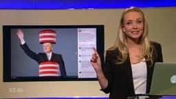eine junge Frau zeigt auf einen Monitor auf dem ein Mensch als Grenzpfosten verkleidet zu sehen ist