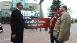 Zwei Männer halten eine Werbeschild für die GroKo