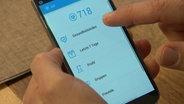 """eine Hand zeigt auf ein Handy mit der App """"Gesundheitsindex"""""""