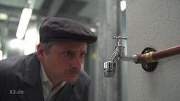 Der Hausmeister starrt auf einen Wasserhahn.