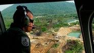 Ein Mitglied einer Eliteeinheit blickt aus einem Hubschrauber auf den Dschungel.