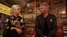 Ina Müller sitzt mit Stefan Effenberg auf ihrem Tresen.