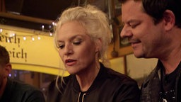 Ina hält Bierdeckel in den Händen und Ingo Appelt schauen auf die Bierdeckel mit ihr.
