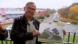 Ein Mann hält ein Bild in die Kamera auf dem Zwei Autos von einer Kunstinstallation aufgespießt wurden (Fotomontage)