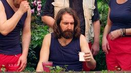 Eine Person, die in Dschungle-Camp-Optiik angezogen ist, schaut leicht angeekelt auf einen Becher Jogurth