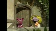 Das Graf zwanzig Kaninchen und eine andere Figur daneben stehen an einer Holztür.