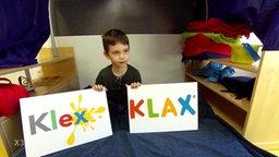"""Ein Kind hält zwei Schilder, auf dem linken steht """"Klex"""" und auf dem rechten ist """"KLAX"""" zu lesen."""