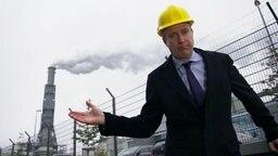 Ein Mann im Anzug mit einem Bauarbeiterhelm steht vor einem Kraftwerk.