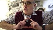 Ein Mann bildet mit seinen Händen ein Dreieck.
