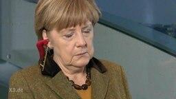 Merkel-Pilot Johannes Schlüter klettert in das Ohr von Angela Merkel