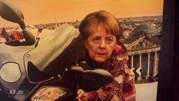 Ein Plakat zeigt Angela Merkel auf einem Motorrad