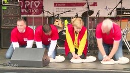 Angela Merkel macht eine Übung zur Wiederbelebung auf einer Bühne mit weiteren Personen