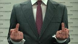 Eine Person im Anzug zeigt seine beiden Mittelfinger in die Kamera