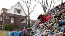Ein sehr großer Müllberg im Garten eines Reihenhausees wird von einer person in Outdoorklamotten bestiegen.