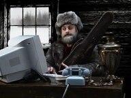 Mann mit Fellmütze sitzt am Computer.