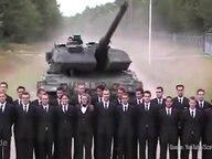 Ein Panzer, davor mehrere Männer in Anzügen.