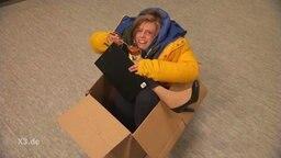 Eine Frau sitzt in einem Pappkarton