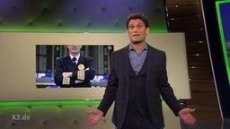 Der Moderator Christian Ehring, im Hintergrund ein Bild eines Piloten der die Arme verschränkt.