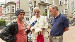 Reporter mit zwei Passanten im Interview