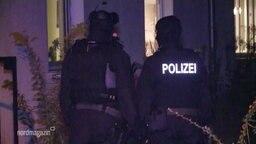 Polizeibeamte vor einem Haus.