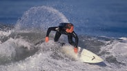 Ein Mann beim surfen. © picture-alliance / beyond/Tips RF