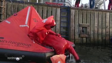 Das Servicepersonal eines Kreuzfahrtschiffes übt, wie sie in ihren rotten Rettungsanzügen Menschen aus dem Wasser und in das Rettungsboot ziehen können.