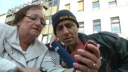 Reporter Rollo betrachtet mit einer Frau ein Smartphone.