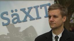 ein Mann vor einem Plakat mit der Aufschrift: Säxit
