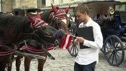 Tobias Schlegl hält eine kleine Österreich-Flagge, an der ein Pferd knabbert.