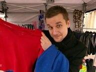 Tobias Schlegl hält einen roten Pullover hoch.