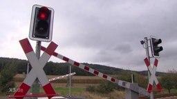 Ein Bahnübergang mit roter Ampel und geschlossenen Schranken.