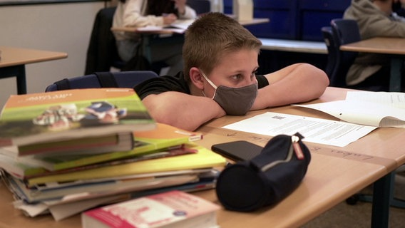 Boy with a respirator has put his upper body on a table.  © NDR