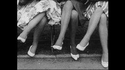 Drei Frauen sitzen auf einer Bank und überschlagen ihre Beine in die selbe Richtung (Archivbild).