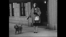 Frau im Pelzmantel spaziert mit Pudel.
