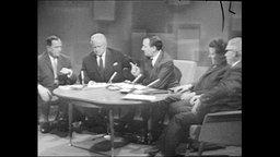 Fünf Männer sitzen an einem Tisch.