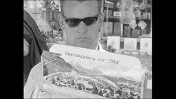 "Tourist schaut Postkarte mit Aufrschrift ""Obersalzberg vor 1945"" an."