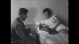 Reporter interviewt eine Frau in einem Krankenhaus-Bett.