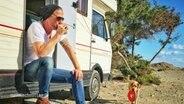Ein Mann sitzt im Eingangsbereich seines Wohnmobils und trinkt aus einem Becher.