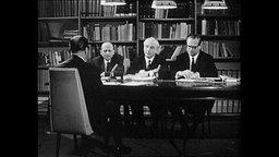 Vier Männer sitzen um einen Tisch und diskutieren (Archivbild)