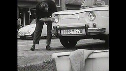 Ein Mann putzt die Scheinwerfer seines Autos (Archiv-Bild).