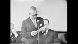 Verteidigungsminister Hassel spricht in ein Mikrofon.