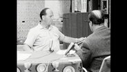 Zwei Männer sitzen an einem Tisch und sprechen in Mikrofone.