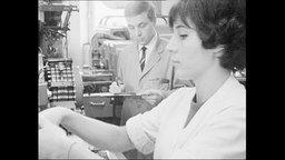 Frau arbeitet an einem Fließband, Mann in einem Kittel macht sich Notizen.