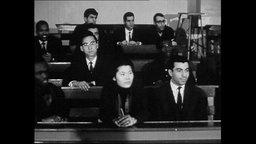 Studierende sitzen in den Reihen eines Hörsaals.