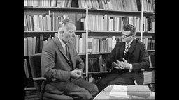 Reporter und Prof. Speer sitzen vor einem Bücherregal.