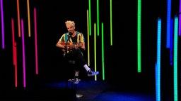 Sänger Jendrik Sigwart singt und spielt mit einer Ukulele auf einer Bühne mit bunten Leuchtstoffröhren.