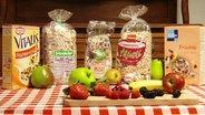 Fünf verschiedene Früchte-Müsli-Sorten im Test: Vitalis von Dr. Oetker, Seitenbacher Müsli, Bio Früchte-Müsli von dm, Früchte-Müsli von Penny und Früchte Hafer-Müsli von Kölln. Im Vordergrund Äpfel, Erdbeeren, Bananen, Brombeeren und Birnen.